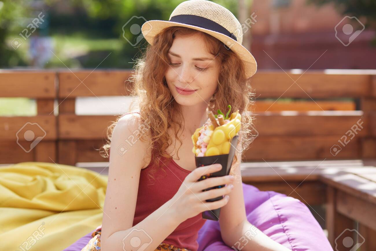 Young woman sitting on farameless chair in park, holding in hands ice cream, wearing burgundy casual t shirt and hat, looks mysteriously down, enjoying to spend summer day outdoor. Recreation concept. - 129221710