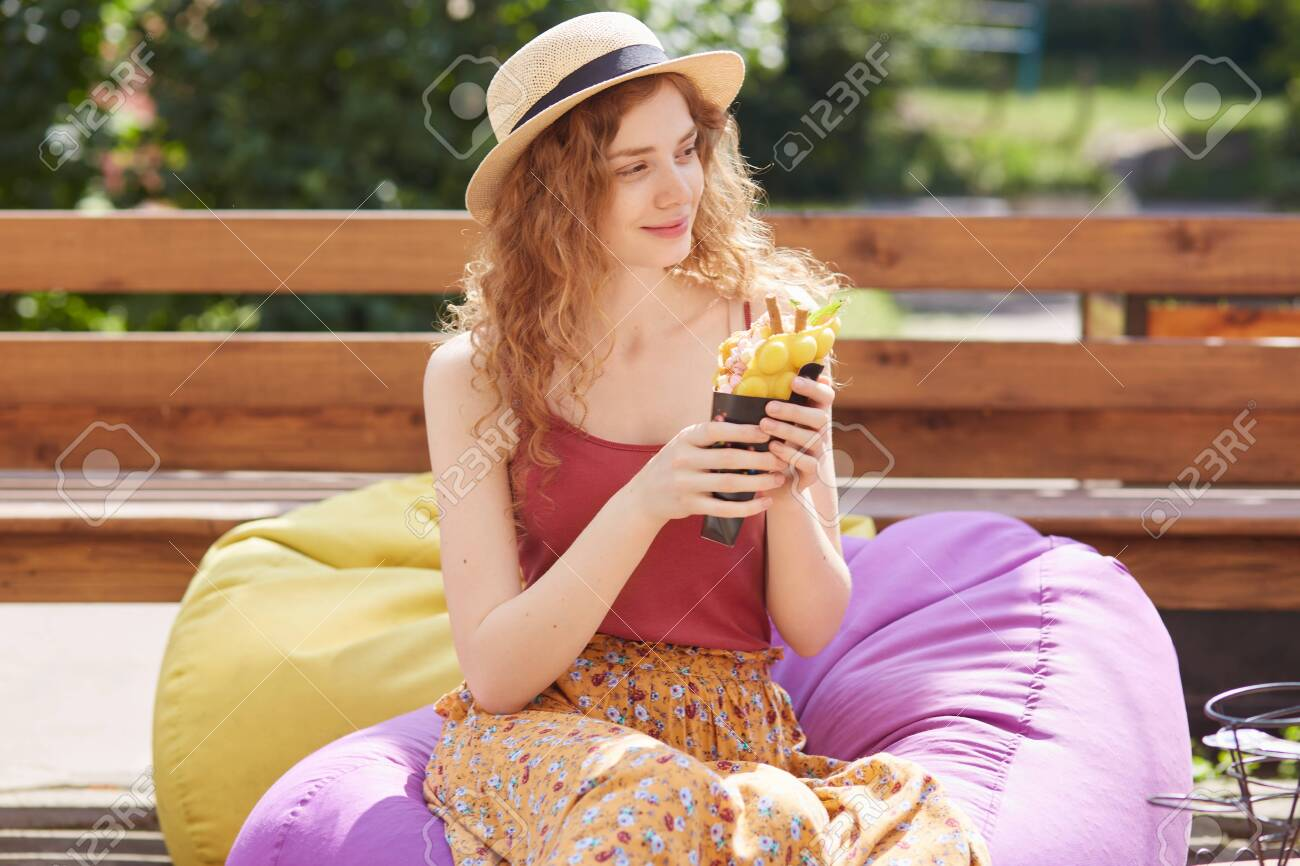 Outdoor shot of young female with foxy curly hair, sits on frameless chair smiling, looking aside and holding big ice cream in her hands, being in park in summer, cools with ice cream in hot weather. - 129221689