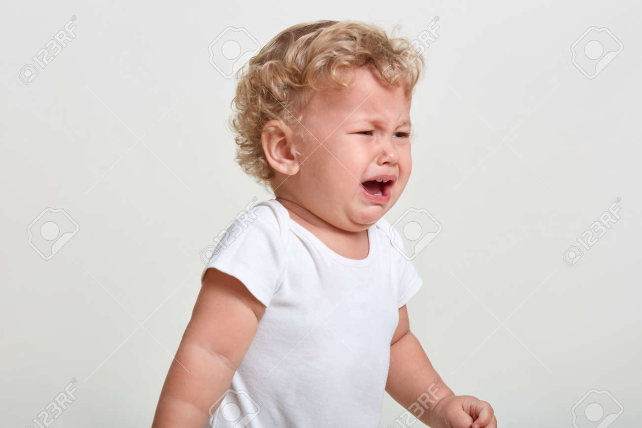 Little boy wearing t shirt cries, being in bad mood, looking away, posing isolated over white background, finding close person, having blond curly hair. - 158497764
