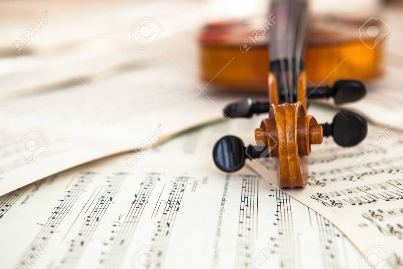 Old violin lying on the sheet of music, music concept - 28873021