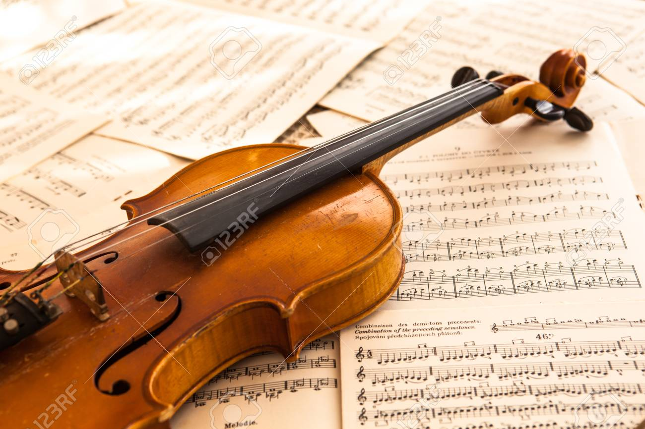 Old violin lying on the sheet of music, music concept - 28914286