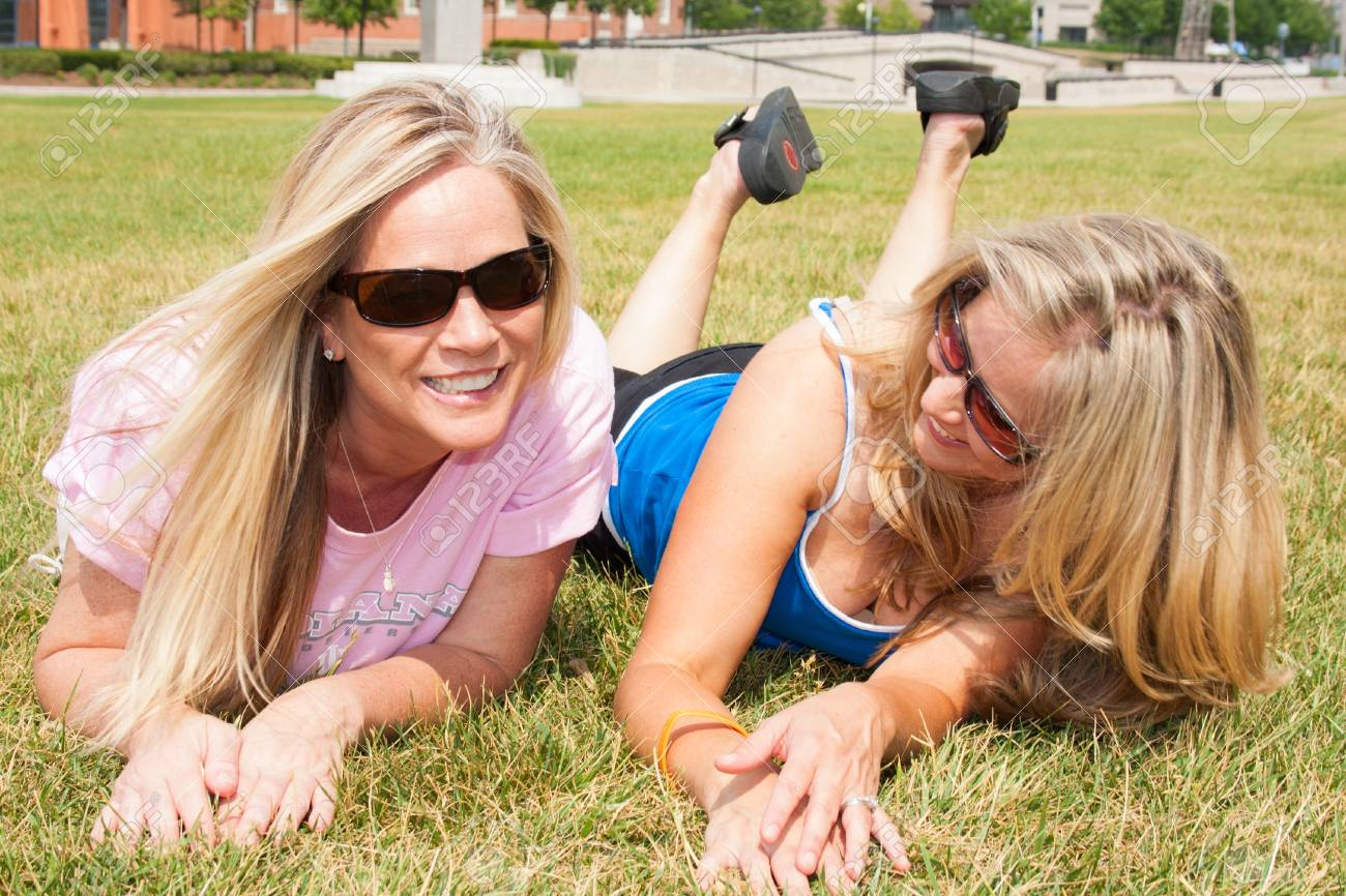 Two woman friends lying on the grass Stock Photo - 13980046