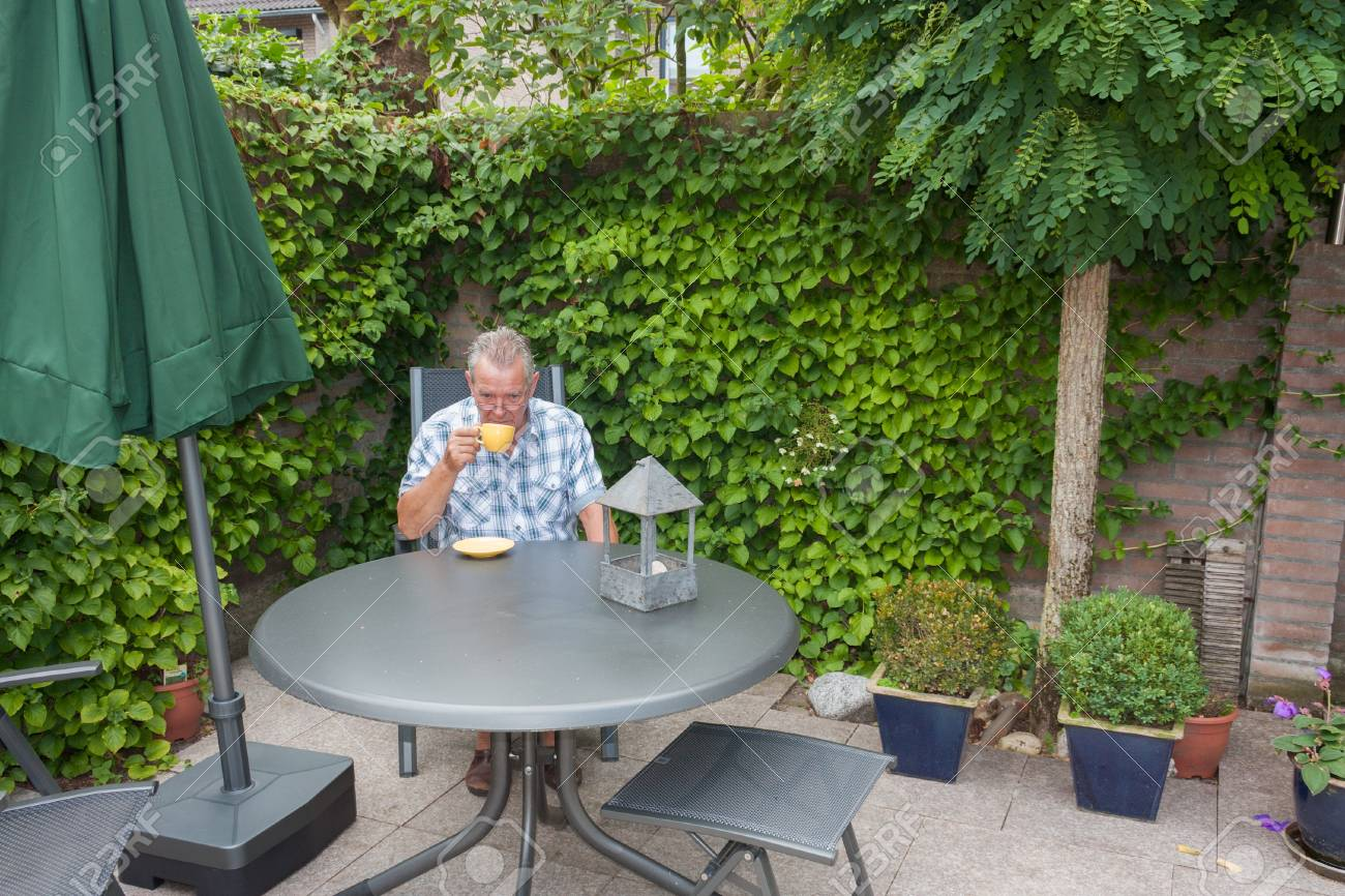 Retired senior Dutch man in deep thoughts whilst drinking a cup of hot coffee  in his back yard Stock Photo - 14731408