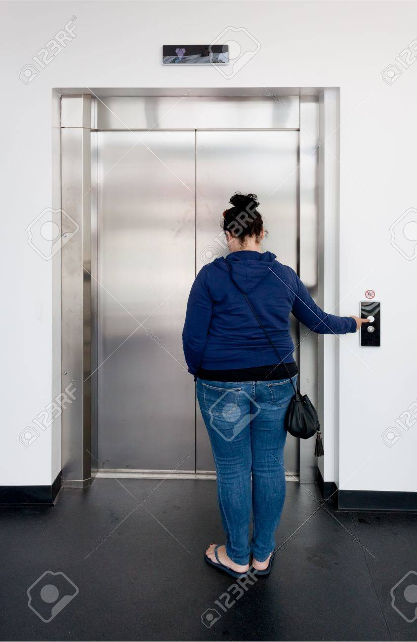 Young woman waiting in bright hallway and calling the elevator Stock Photo - 14950757