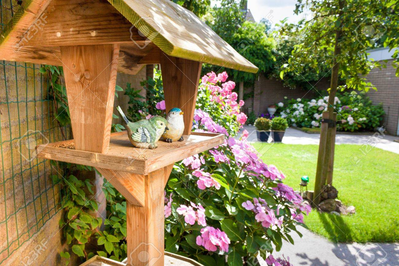 bird house in backyard with two stone birds stock photo picture