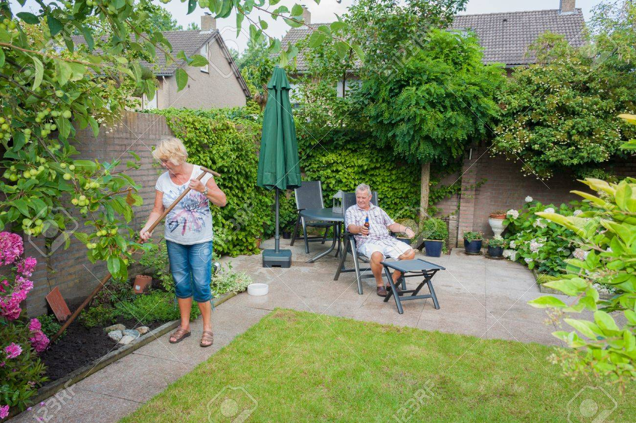 Actively retired Dutch seniors in a Typical display of gender roles where the Wife is gardening and the husband is relaxing and having a beer Stock Photo - 15382987