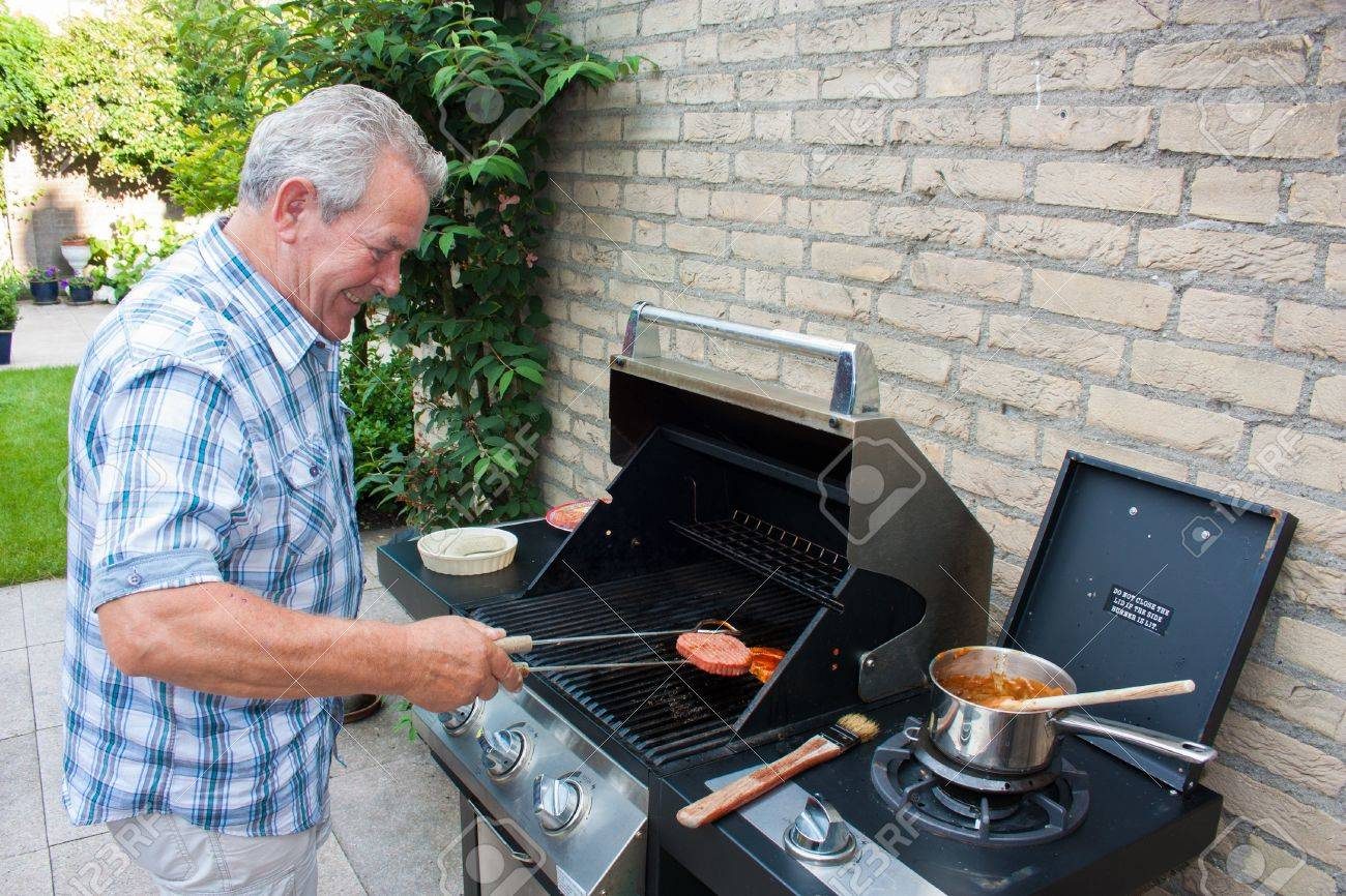 Retired dutch senior man grilling hamburgers in his back yard on a summer day Stock Photo - 15812408