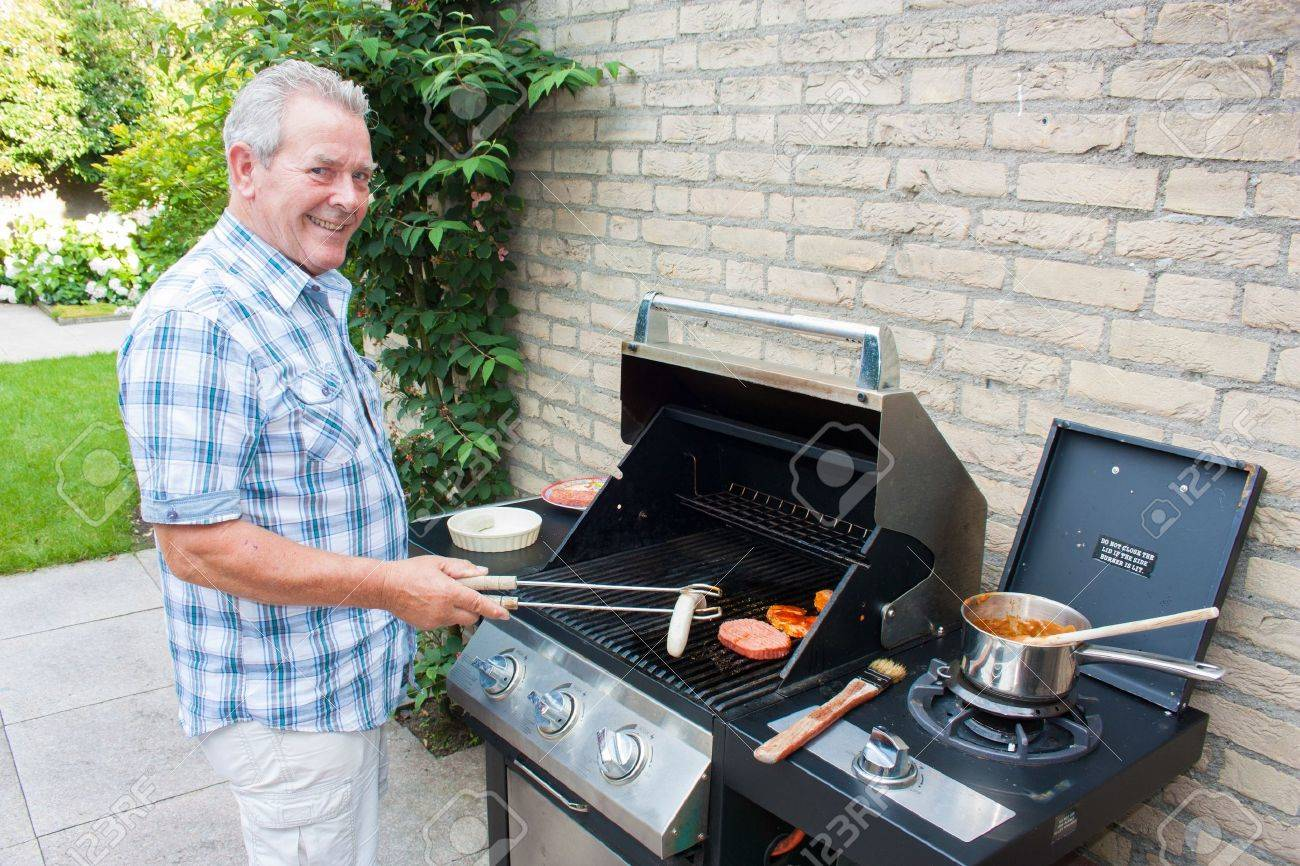 Retired dutch senior man grilling meat in his back yard on a summer day Stock Photo - 15812407