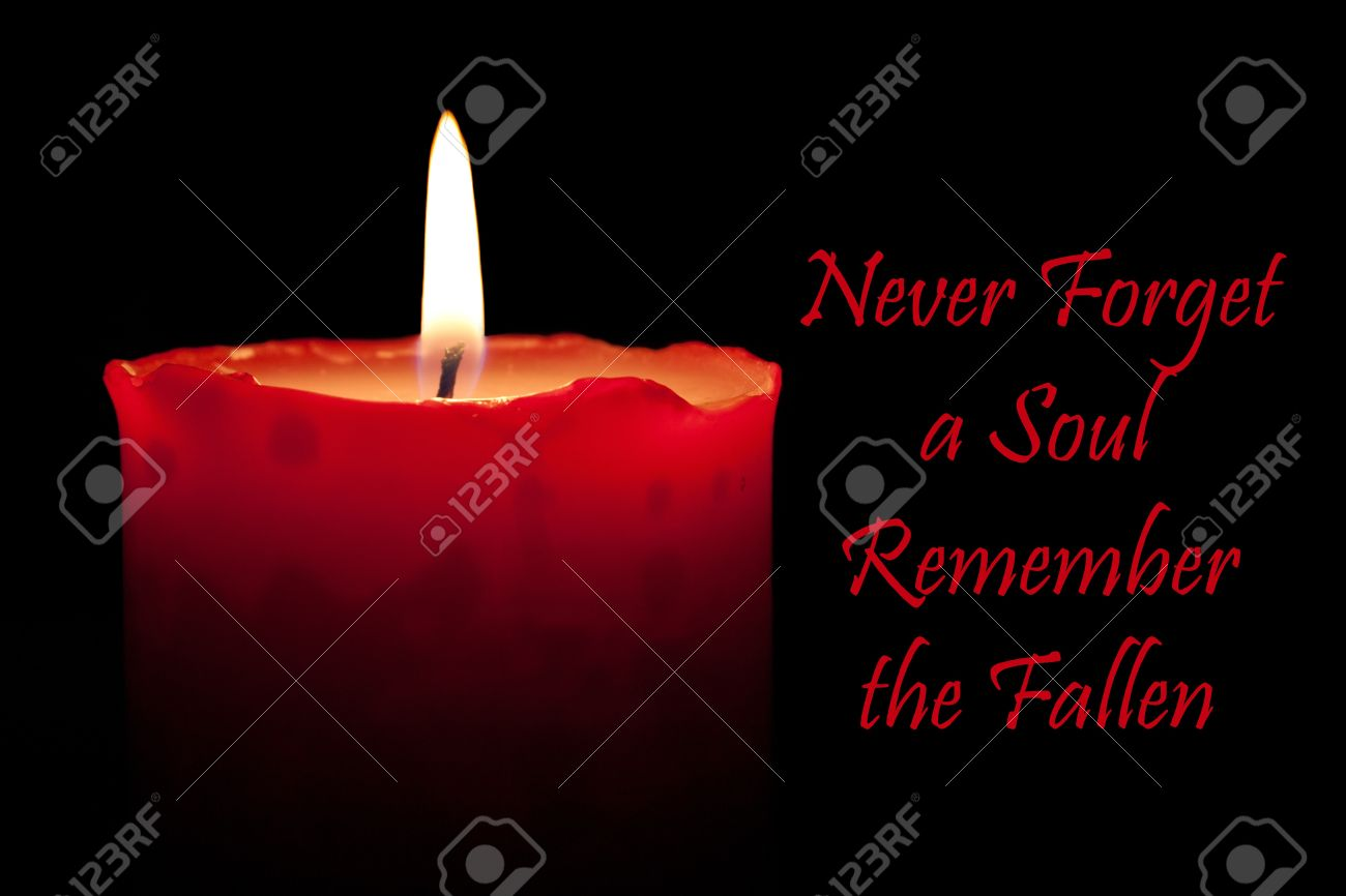 Never forget a soul remember the fallen written next to a burning red candle Stock Photo - 19351932