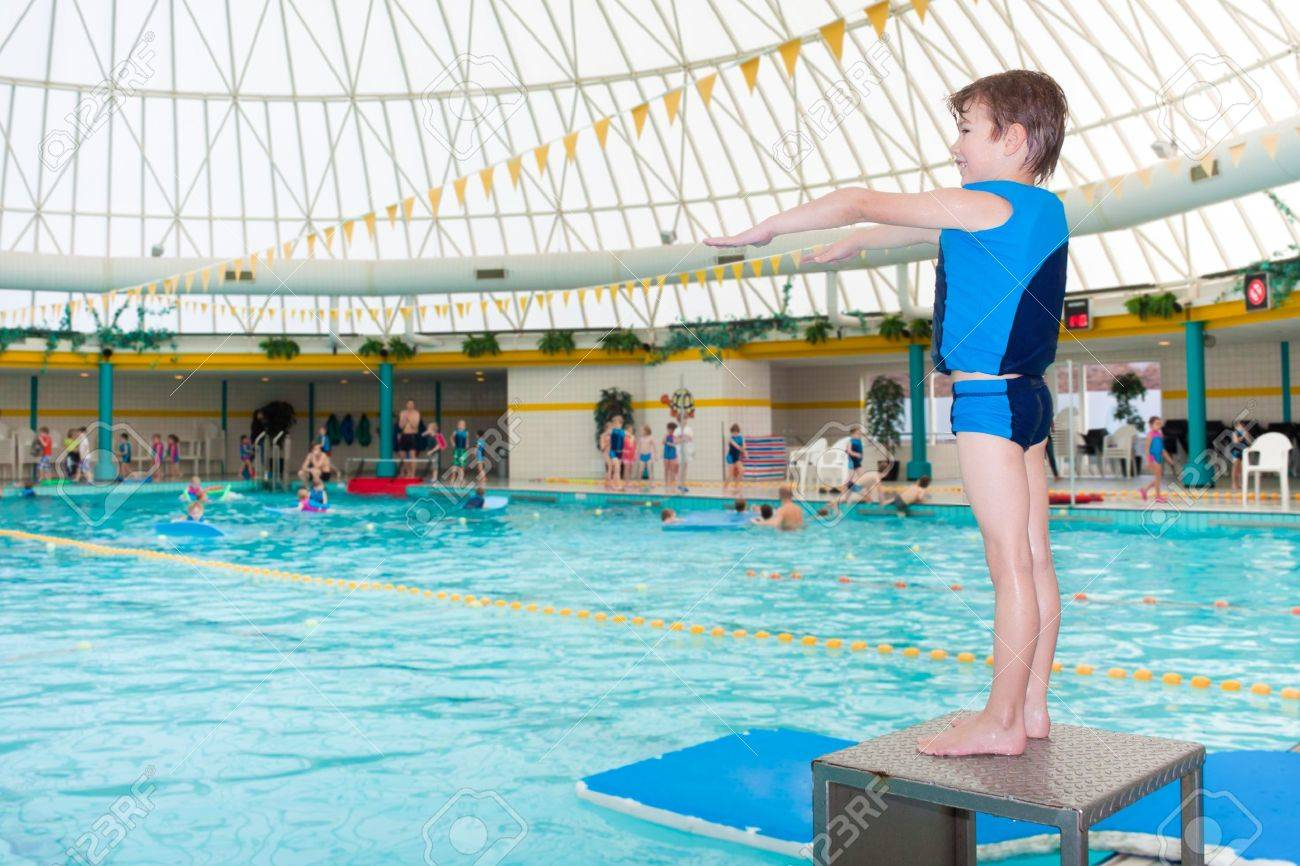 Elegant Little Boy In Swimming Pool Wearing Blue Life Vest Ready To Take A Dive  Stock Photo