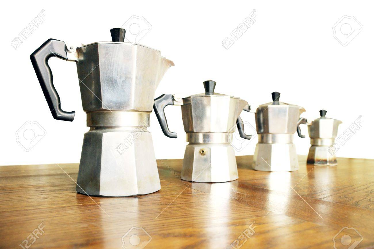 photo of four typical italian coffee machines on the wood table and white background stock photo