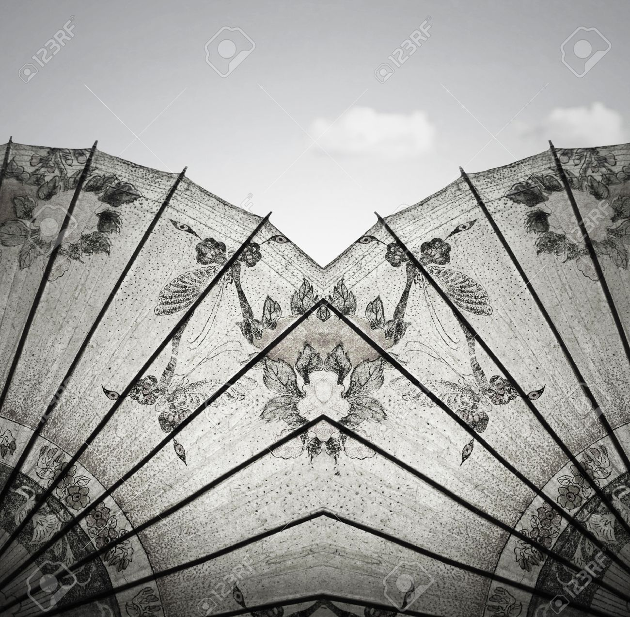 Detail of a beautiful vintage decorative rice paper chinese umbrella with sky and cloud in the background in black and white - 15030734