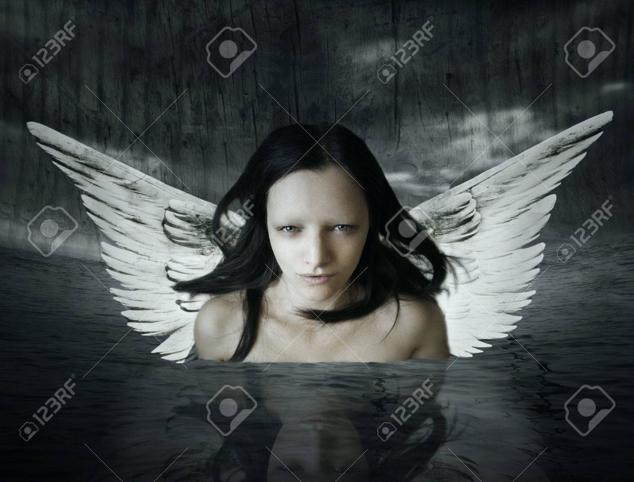 Angelic being that comes out of the water in a setting dark background - 15862756