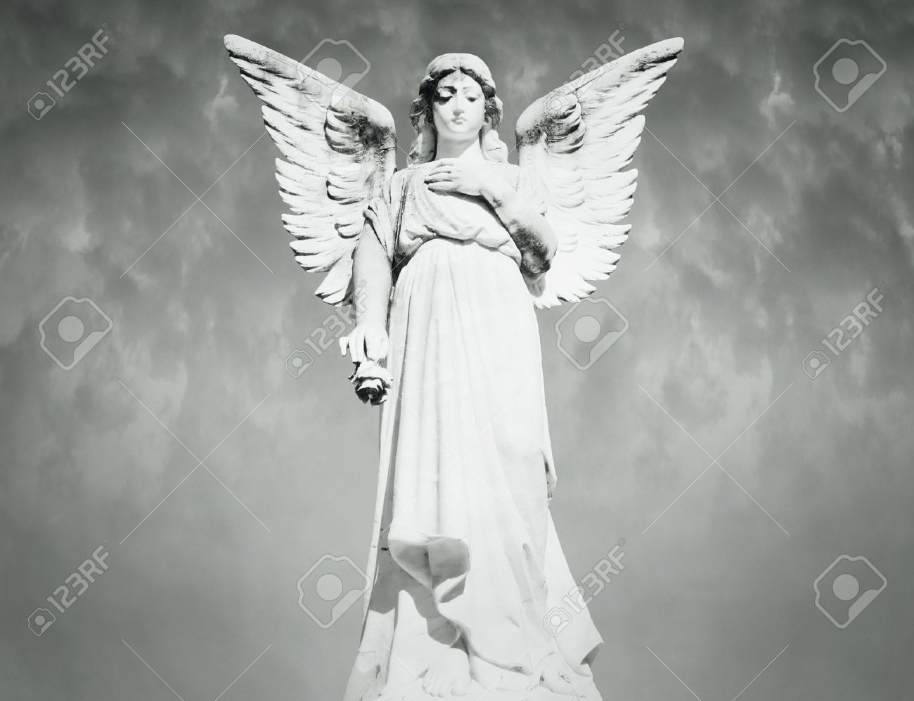 Beautiful full length of an angel with a cloudy sky on the background in black and white - 17185314