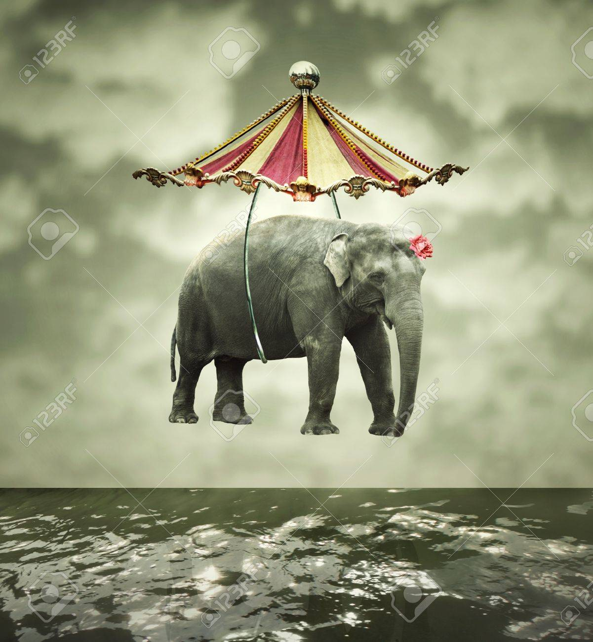 Fanciful and artistic image that represent a flying elephant with circus tent above the water - 17452945