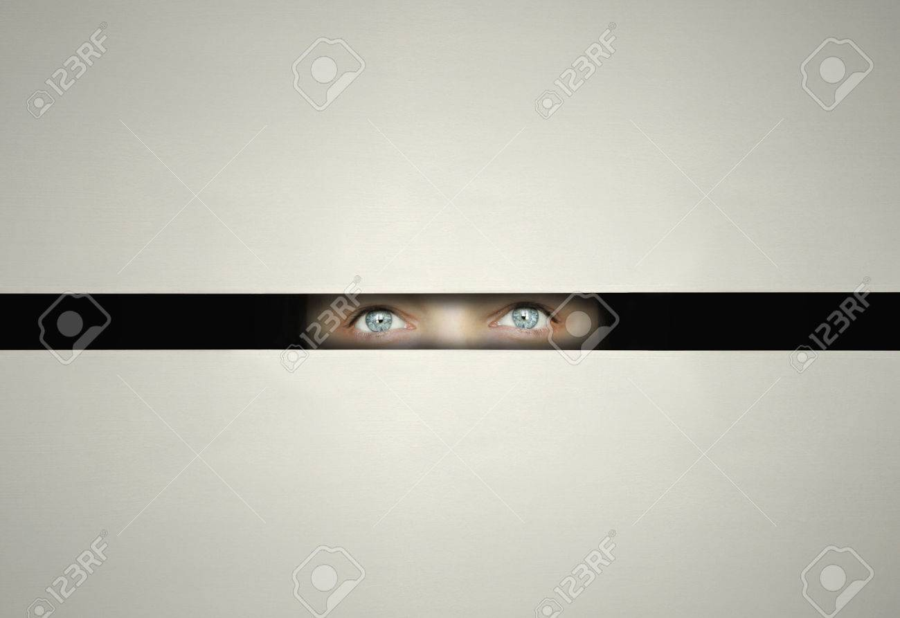Conceptual eyes watching throw a slit with curiosity in the darkness - 24775921