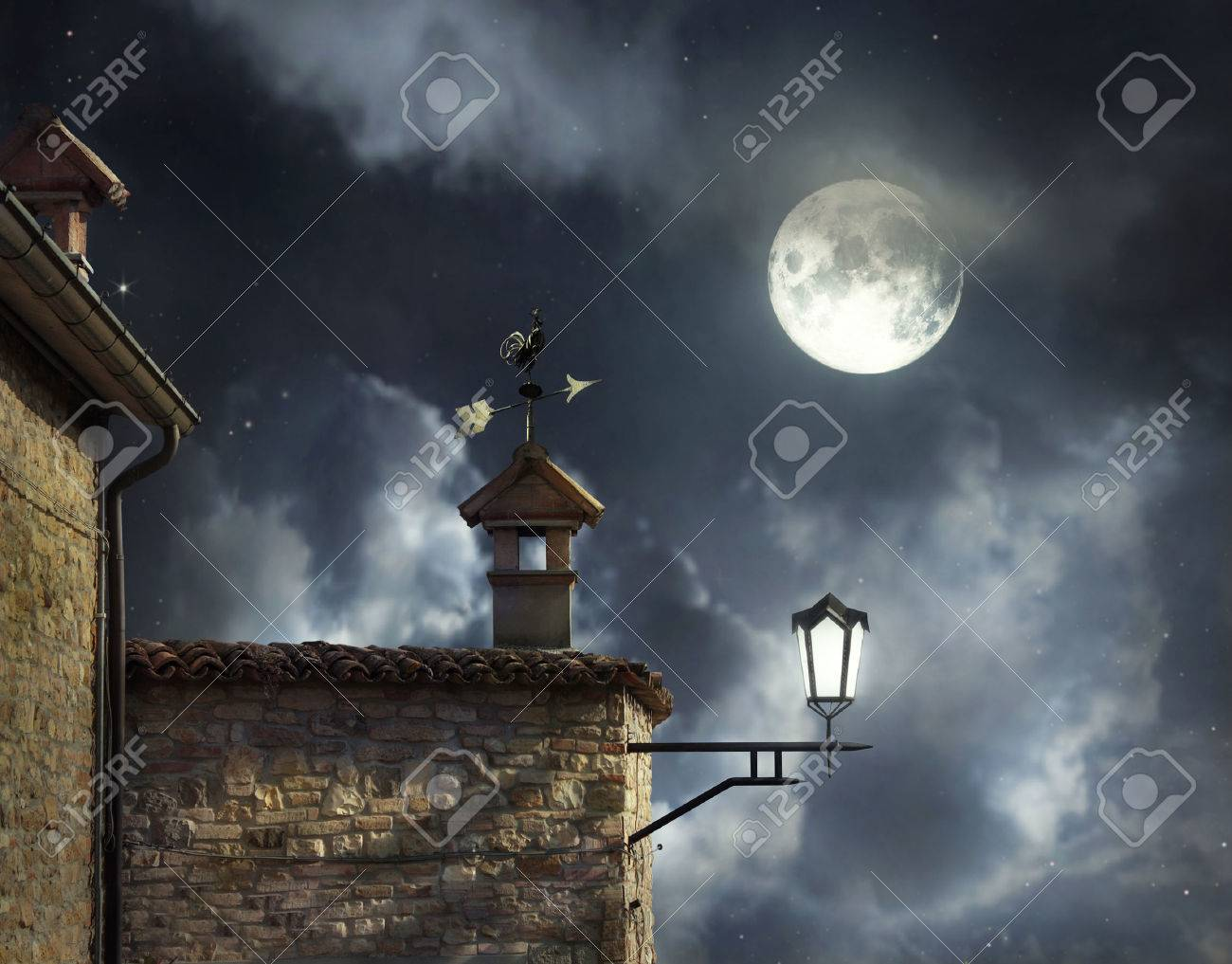 Antique roofs with weather vane rooster and chimneys in a beautiful night sky with full moon and clouds - 38616860