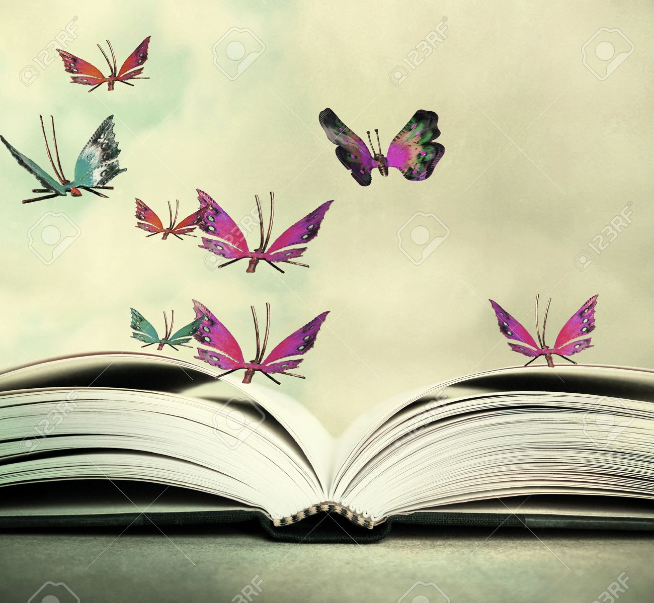 Artistic image of an open book and colorful butterflies that hover in the sky - 59790405