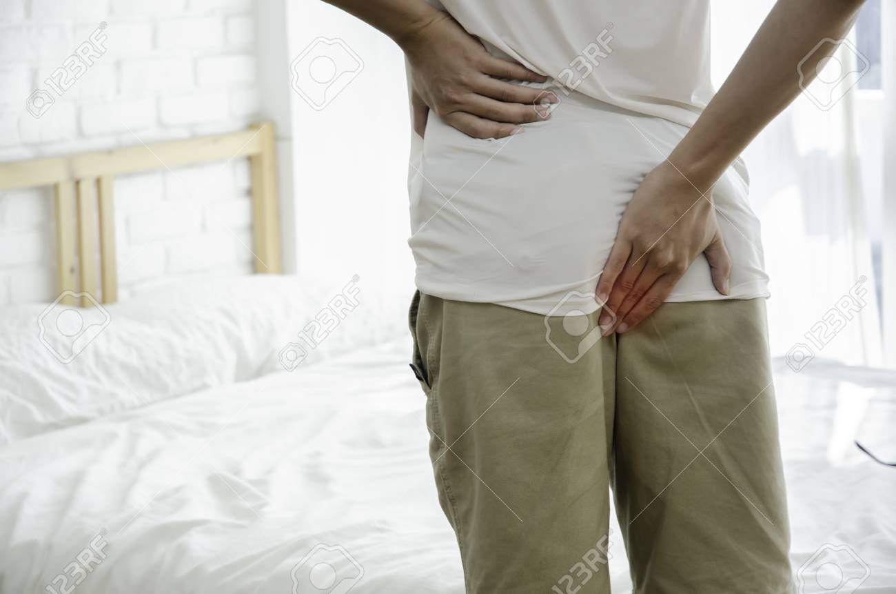 Men put their hands on the buttocks. Have anal pain.The man stands in