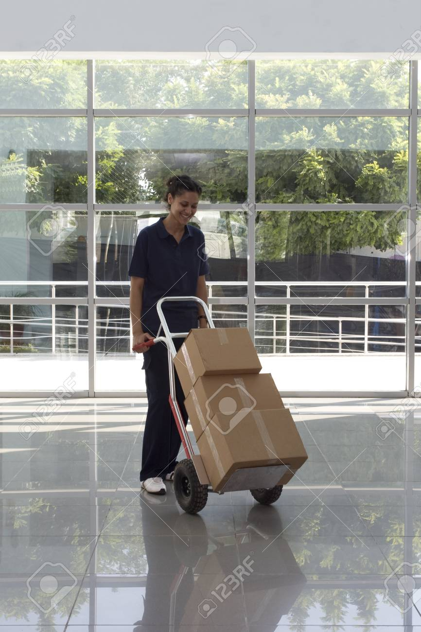 Side view of delivery woman in uniform pushing stack of cardboard boxes on dolly  Stock Photo - 10003466