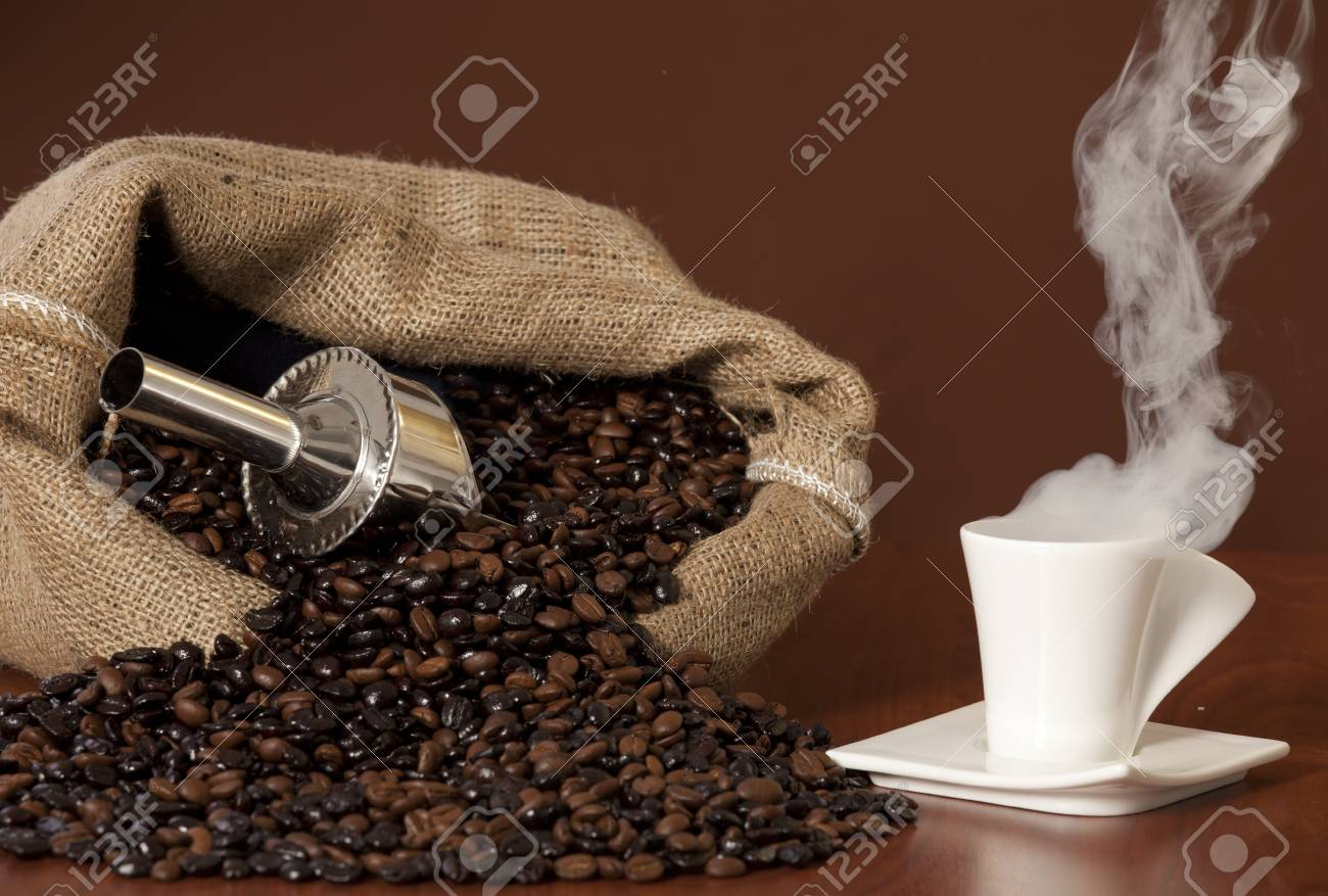 Coffee cup with burlap sack of roasted beans on rustic table Stock Photo - 17006271