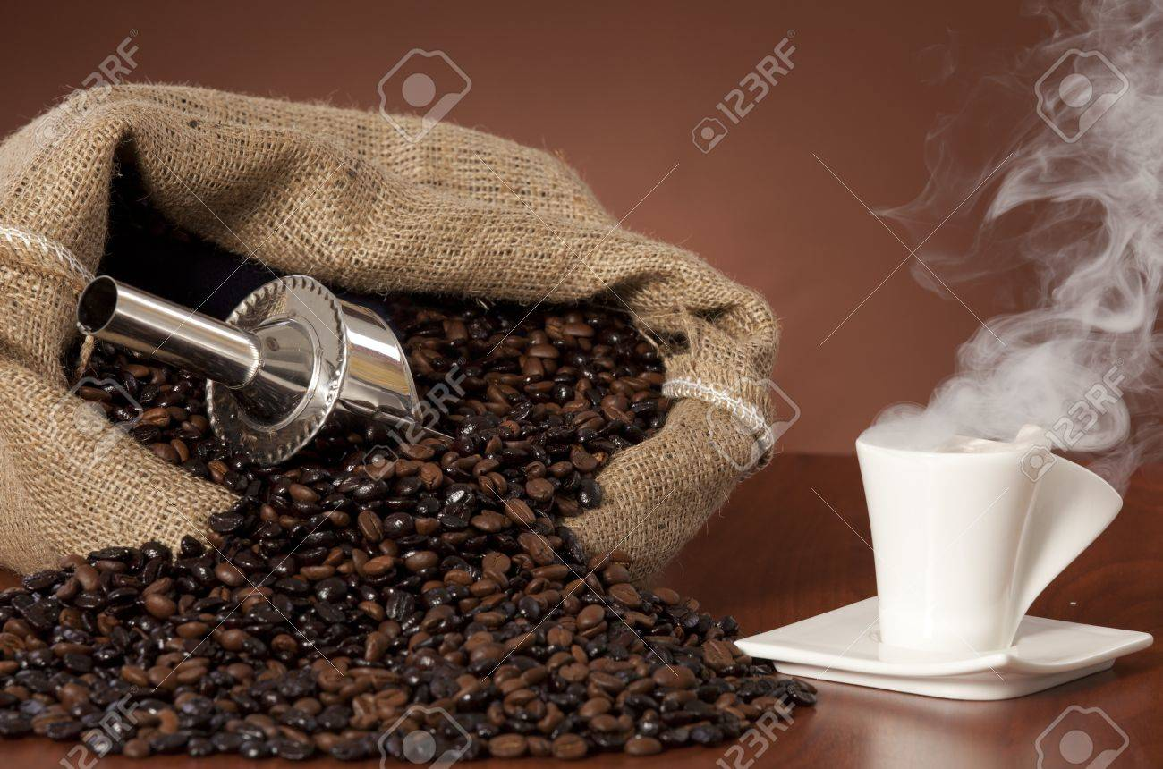 Coffee cup with burlap sack of roasted beans on rustic table Stock Photo - 17006265