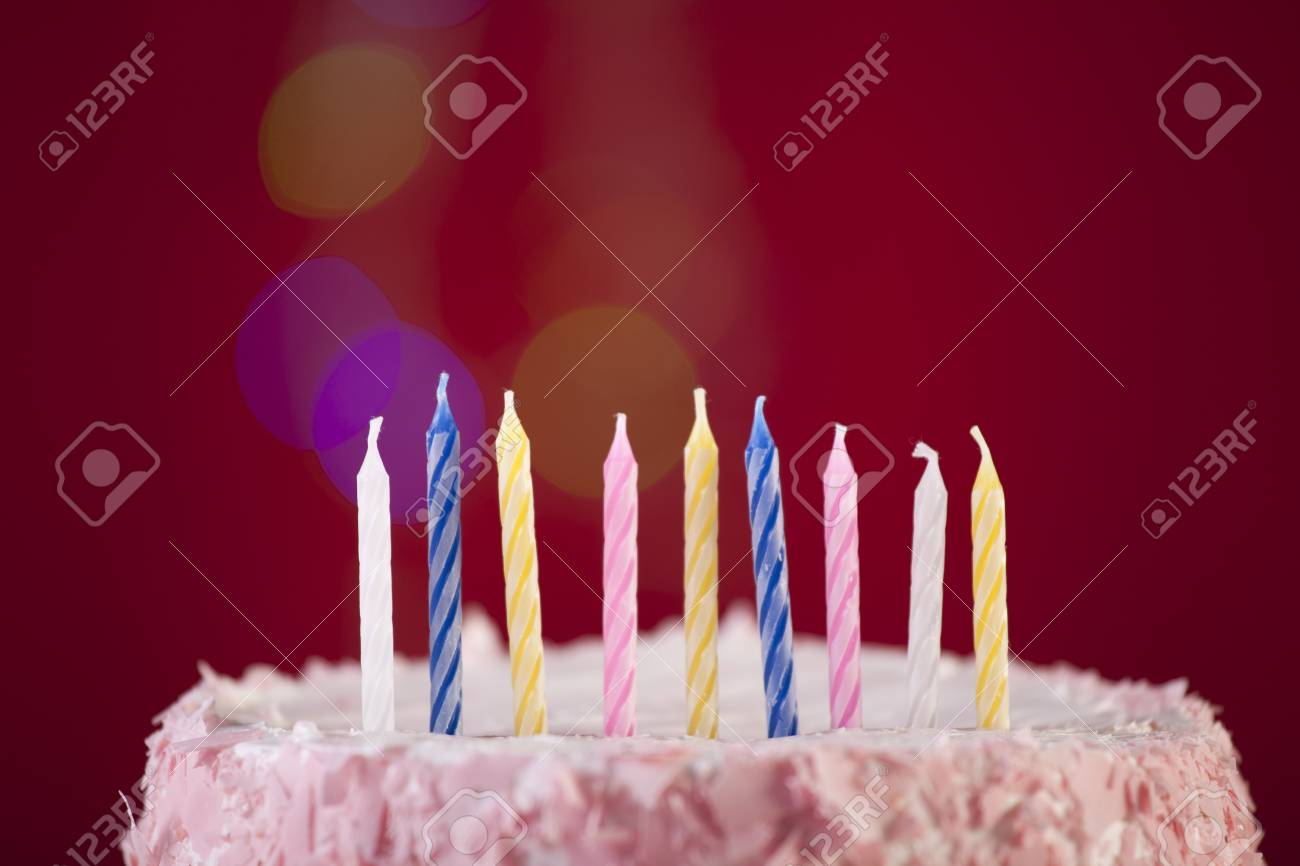 Happy Birthday Cake Shot On A Red Background With Candles Stock