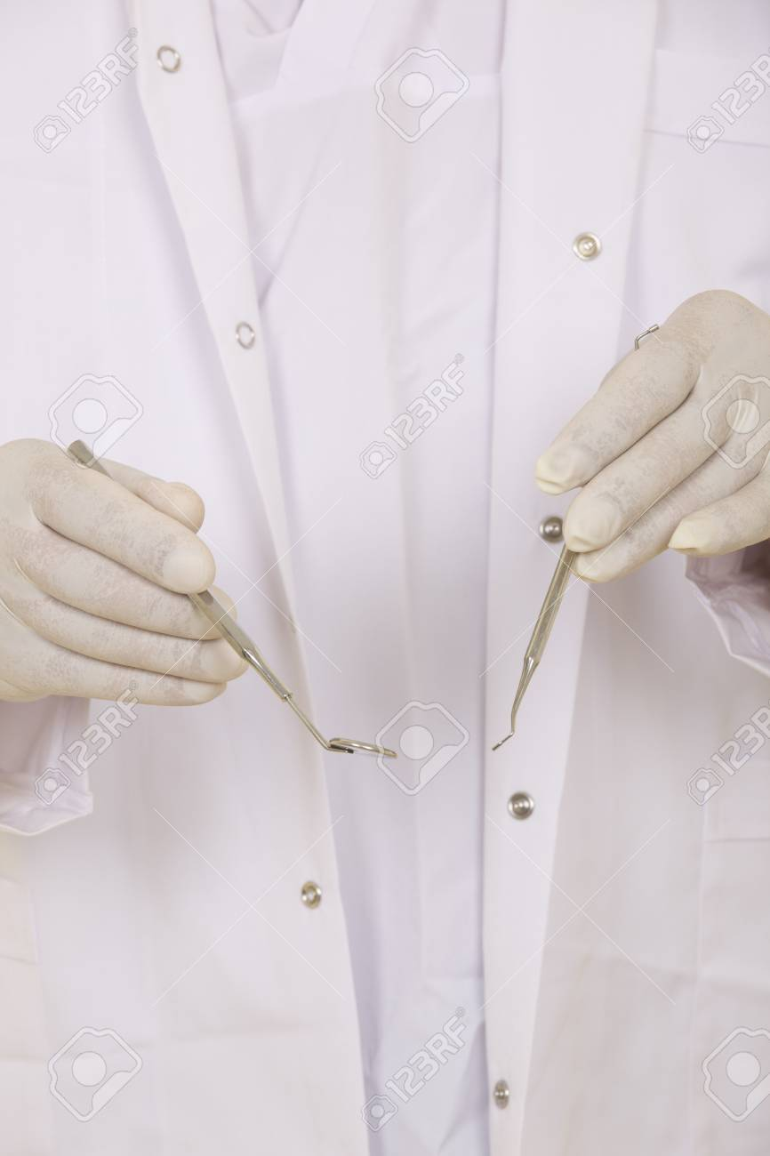 A dentists hands in white medical gloves with dental tools Stock Photo - 20677740