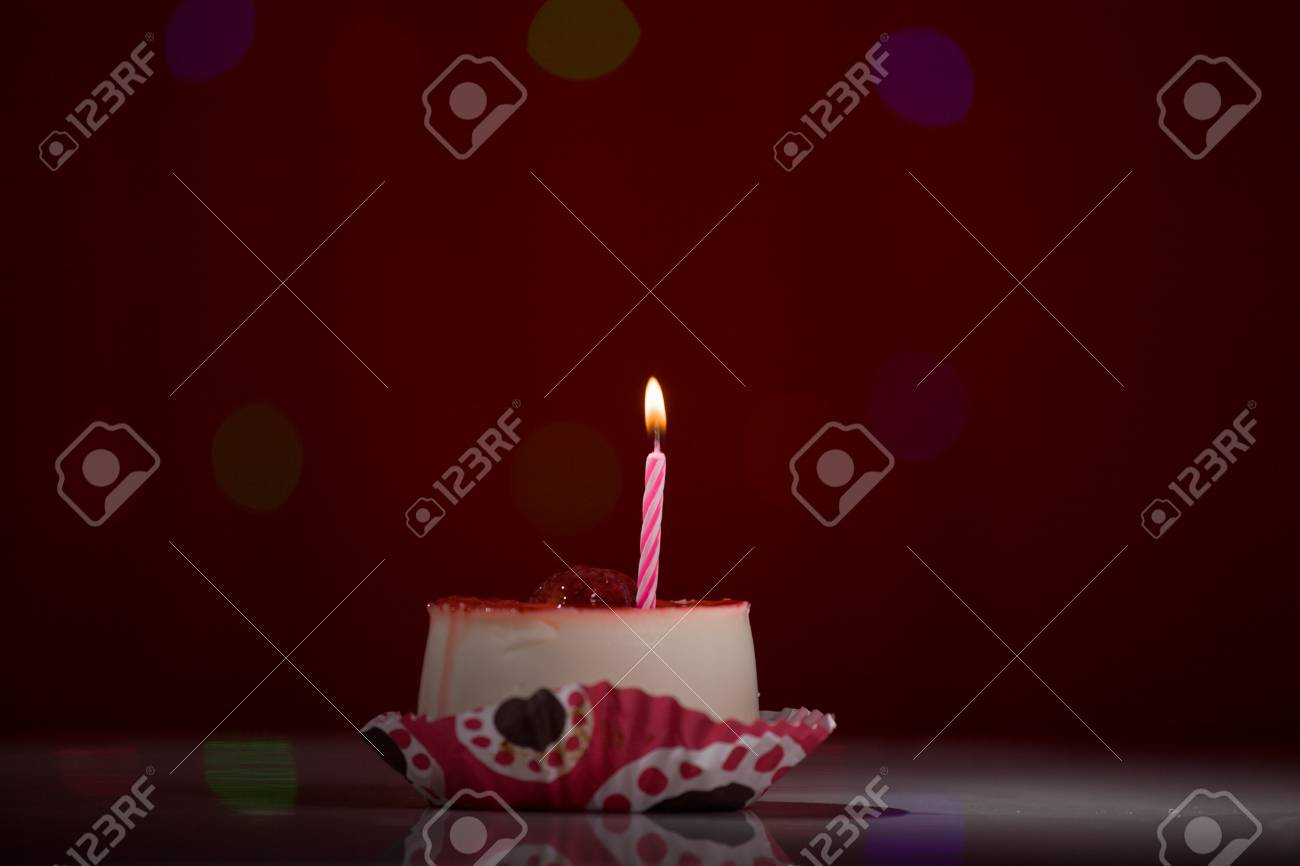 Happy Birthday Cake Shot On A Red Blurred Background With Candles Stock Photo