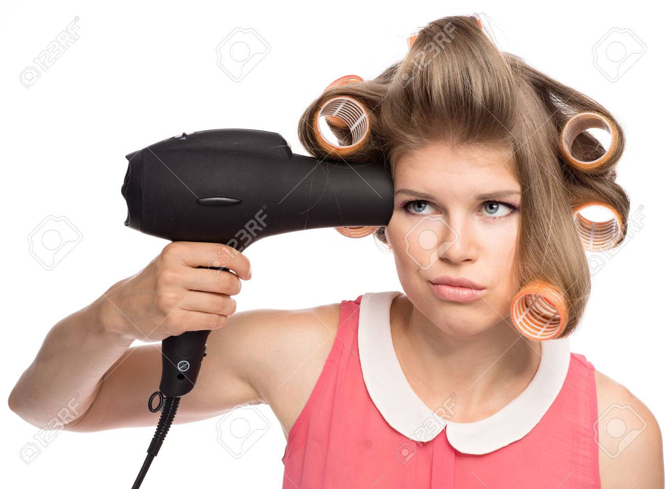 Stressed woman in hair curlers preparing for a date  Pretty blond female model with hairdryer  Isolated over white background Stock Photo - 22677993
