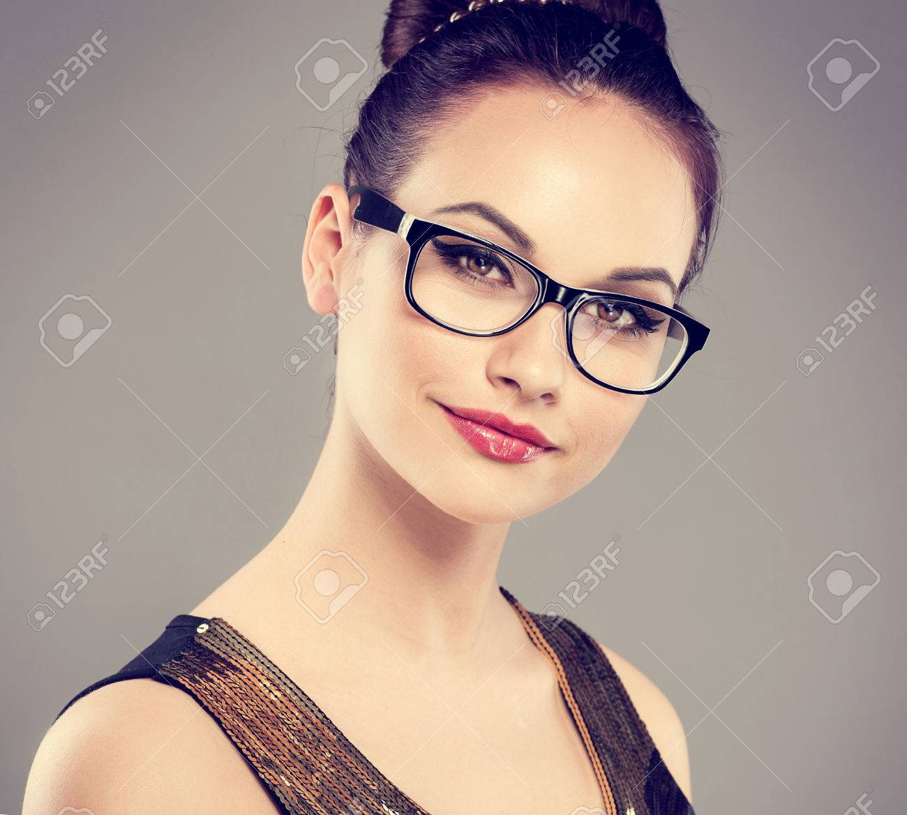 Close-up portrait of fashion glamour model wearing spectacles. Young attractive Caucasian woman posing in studio looking at camera. - 39873257