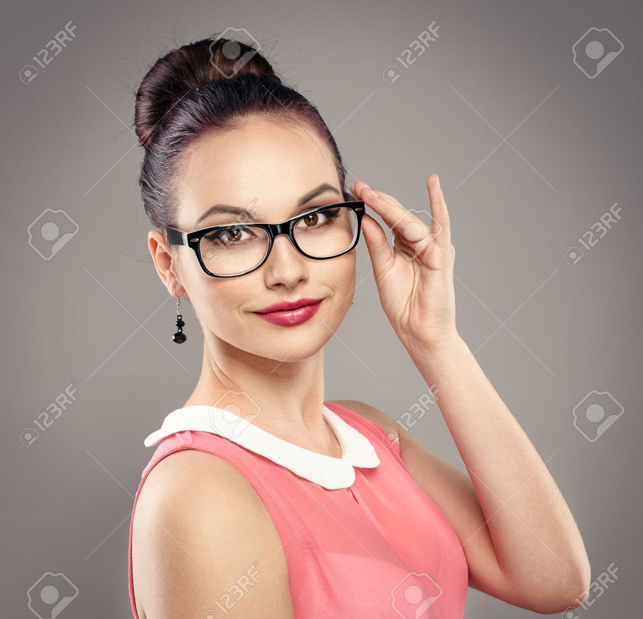 Close-up portrait of fashionable brunette woman with professional hairdo in eyeglasses. Young beautiful female model wearing spectacles posing in studio. - 39873261