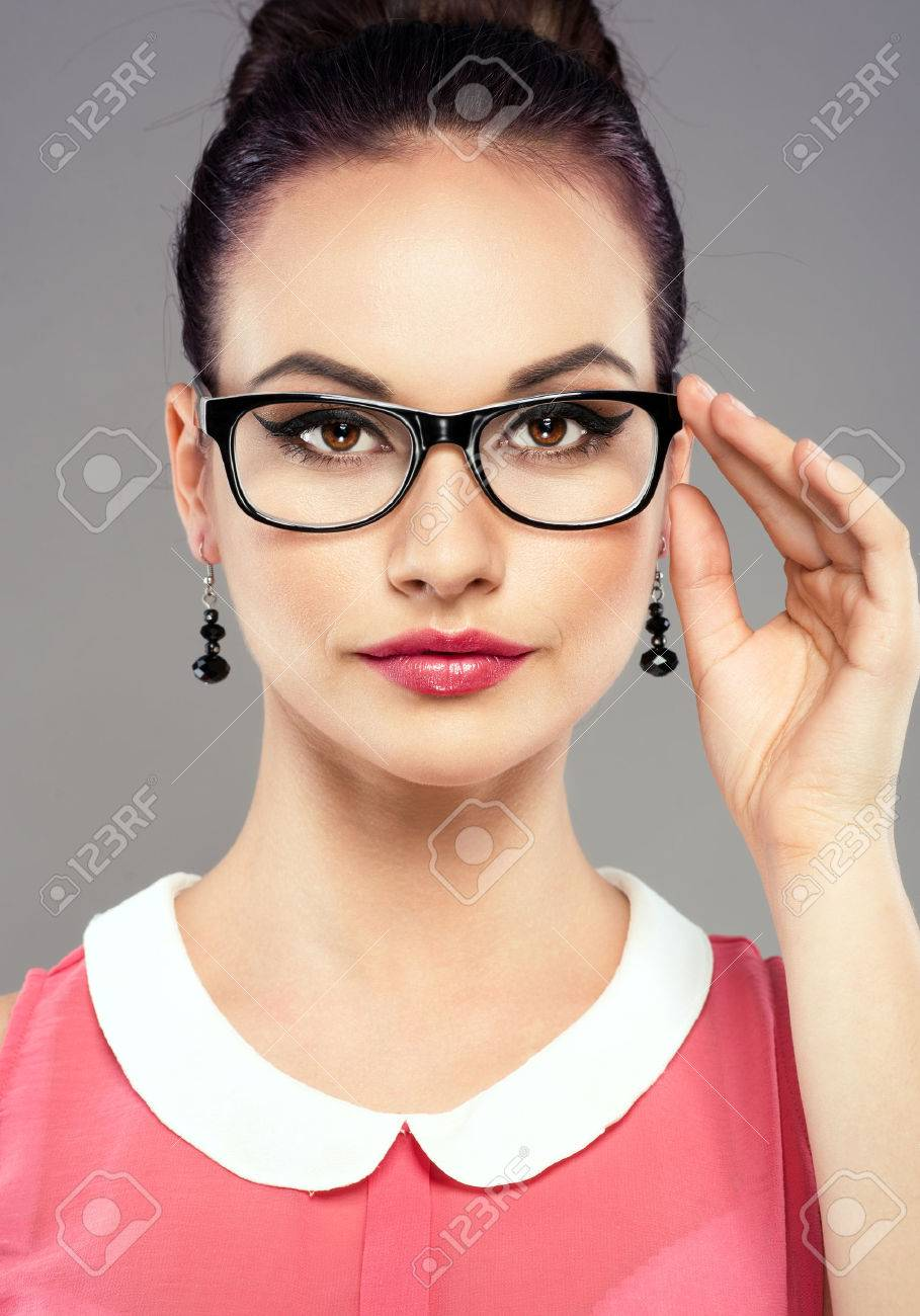 df148fc44e Foto de archivo - Lanzamiento del estudio de la joven morena muy femenina  tocar sus lentes ópticos. Retrato de la chica de estilo retro con  maquillaje ...