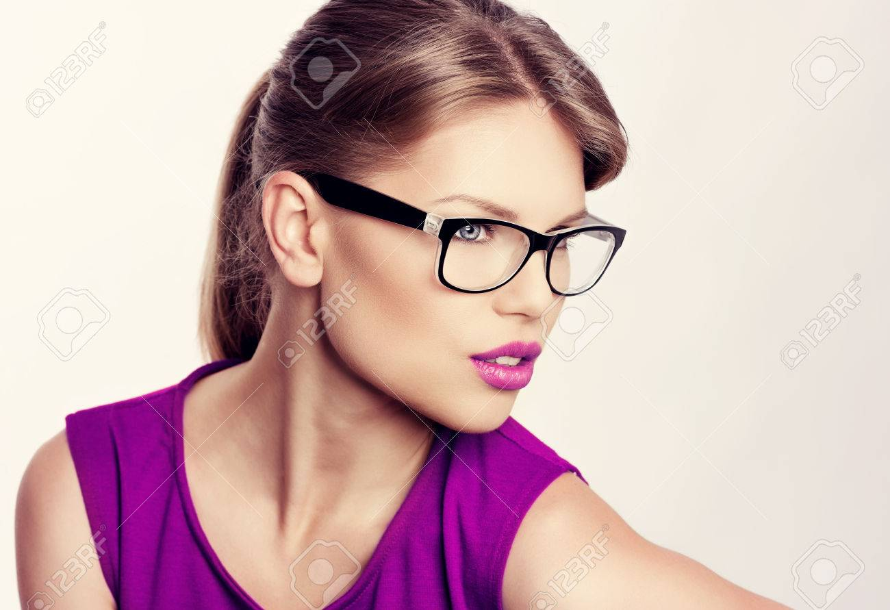 Close-up portrait of beautiful young blonde wearing stylish eyeglasses with purple lips. Attractive Caucasian businesswoman in spectacles. - 39873246
