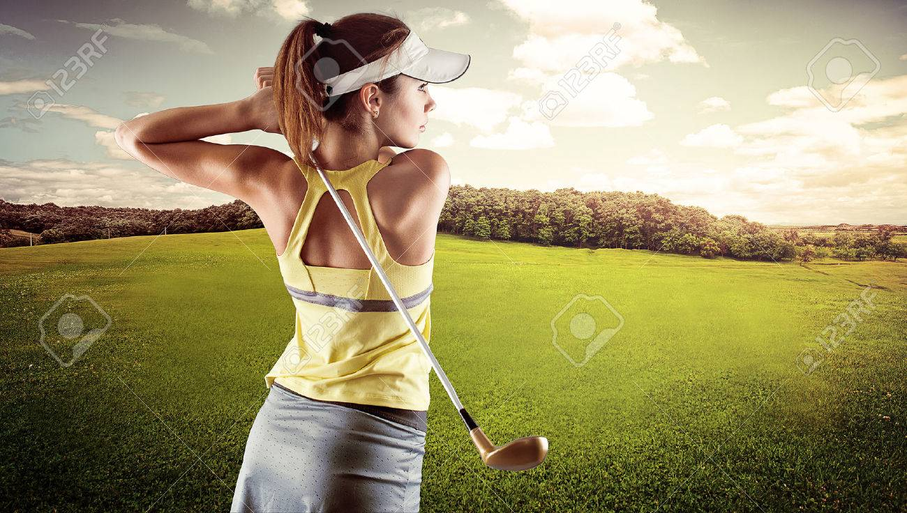 Young female in sportswear playing golf on green field. Active fresh Caucasian woman swinging with golf club. - 39668294