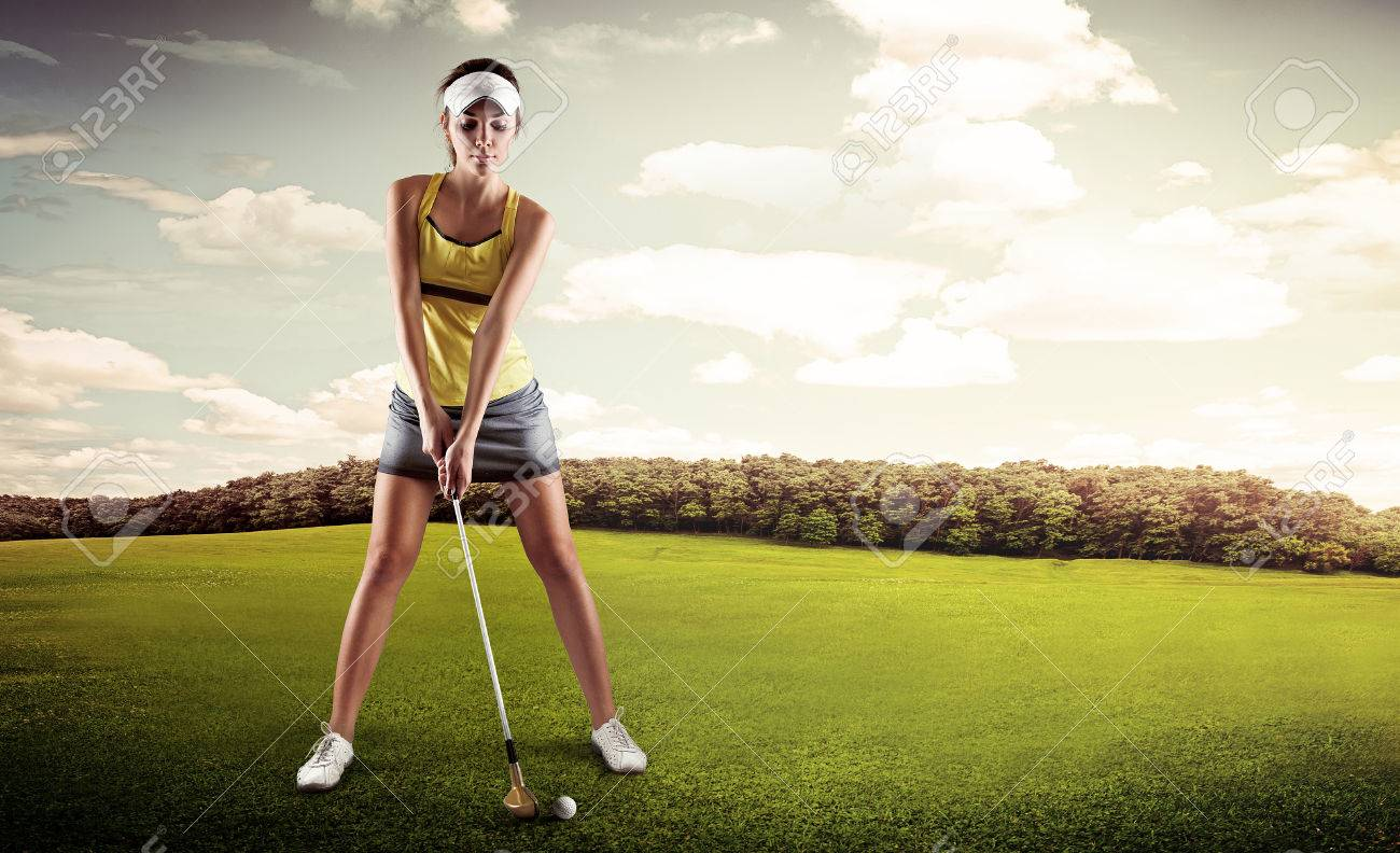 Portrait of female golfer with golf club teeing-off on the nature. Young sporty woman player standing in golf position ready for hit. - 39873247