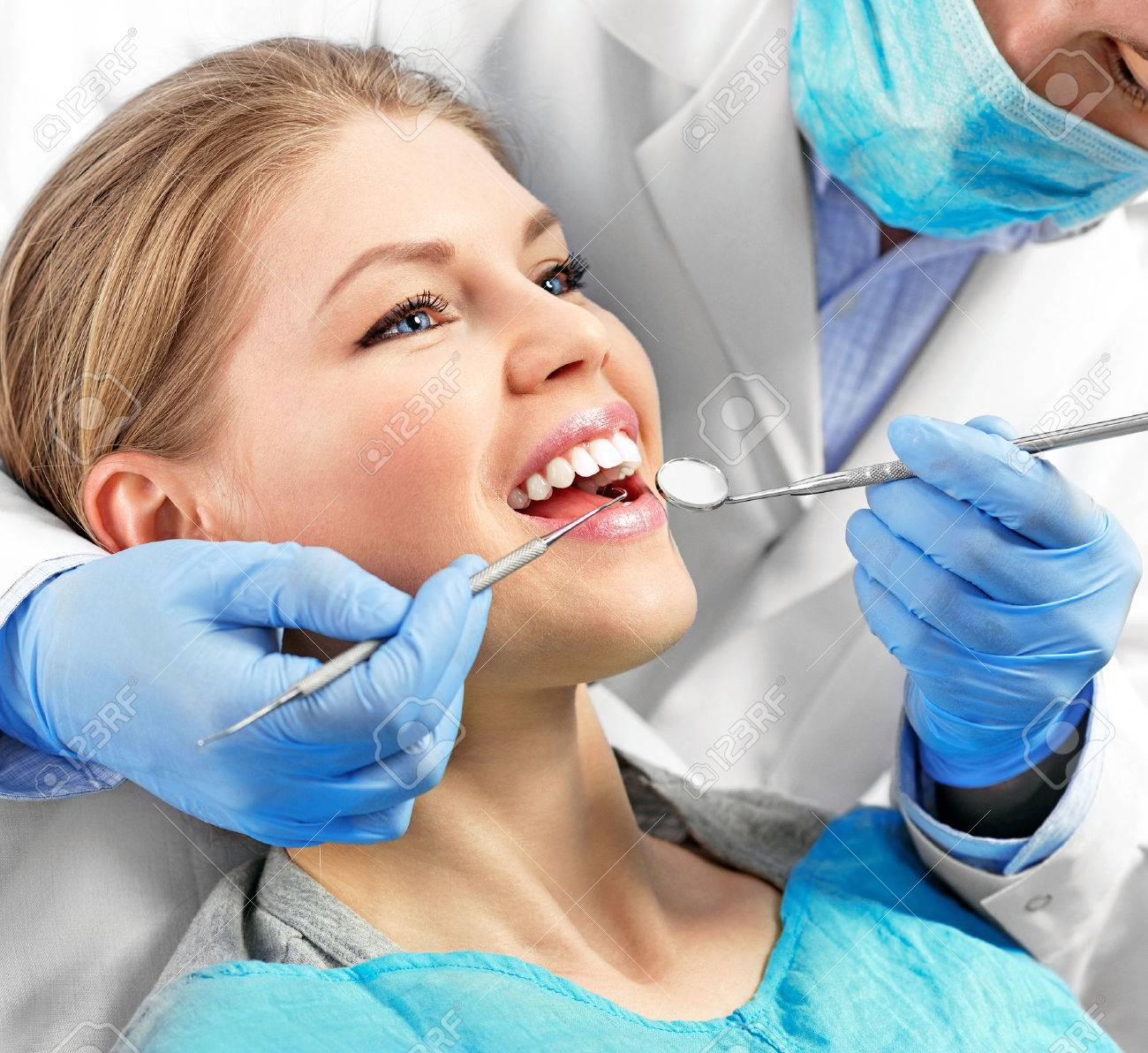 Dental health. Male dentist curing a female patient. - 39370790
