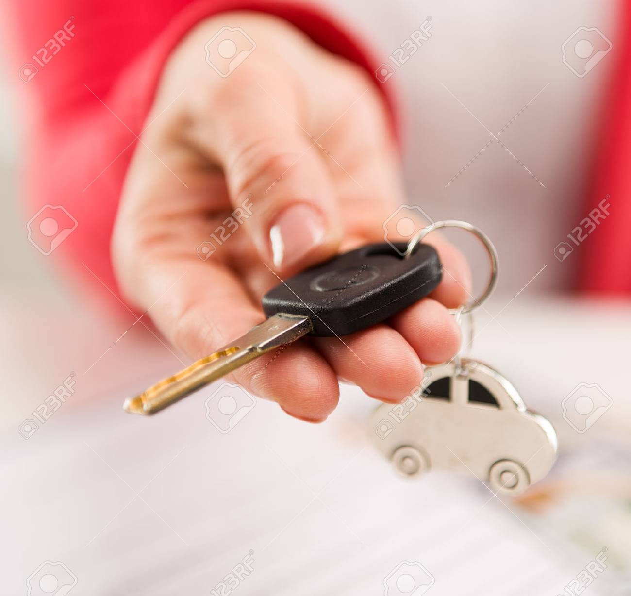 Closeup of female hand giving car key to buyer in automotive dealer - 39619474