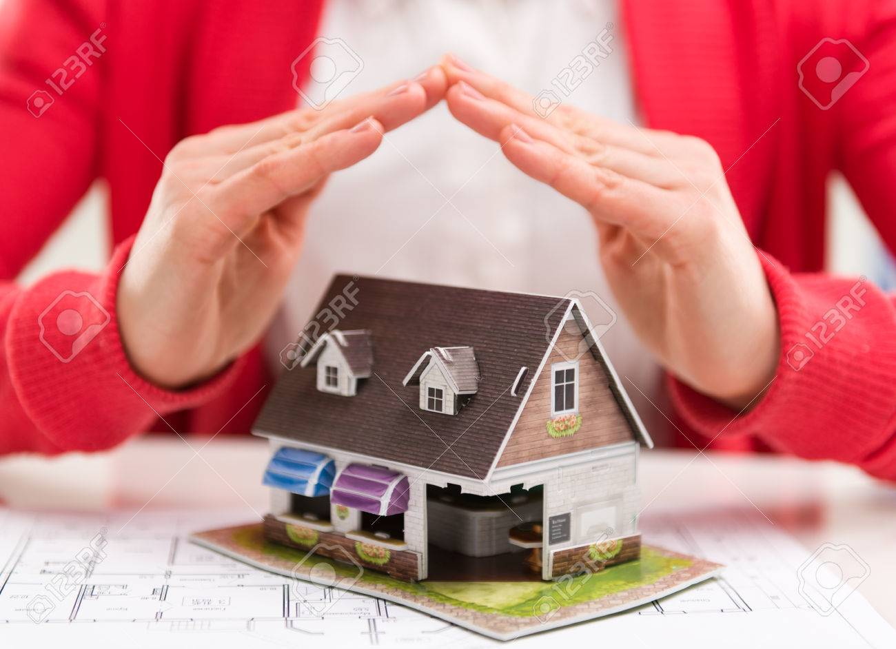 Close-up of mortgage agent hands with family house model in real estate agency. Concept of real estate loan agreement. Shallow depth of field. - 39619497