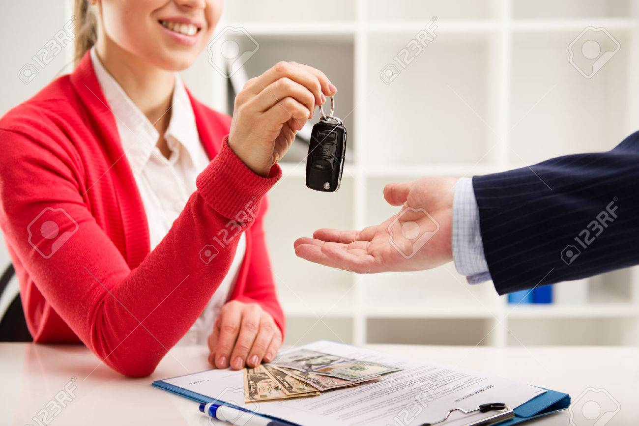 Rental contract. Transport purchase. Woman automotive dealer offering car key to buyer. Shallow depth of field. - 42189925