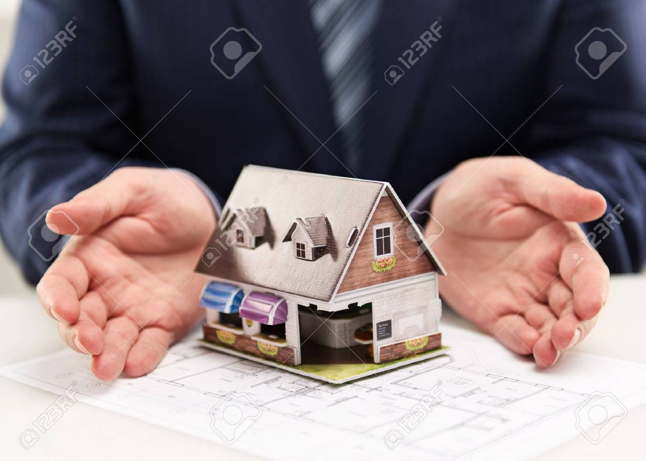 Male house agent showing family residence model to customers. Real estate agreement concept. Shallow depth of field. - 39598924
