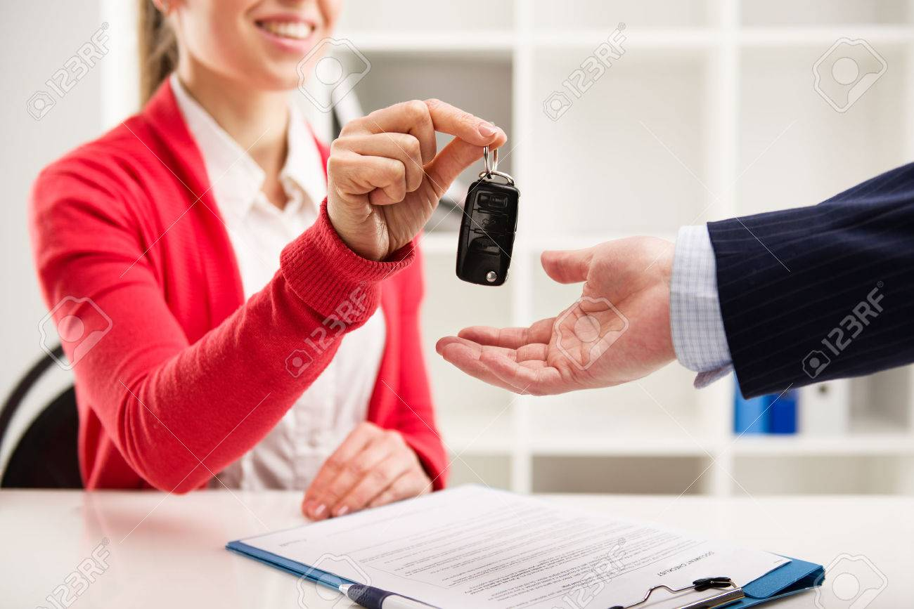Female car agent giving key to male customer for test drive. Partnership and contract signing. - 39598925