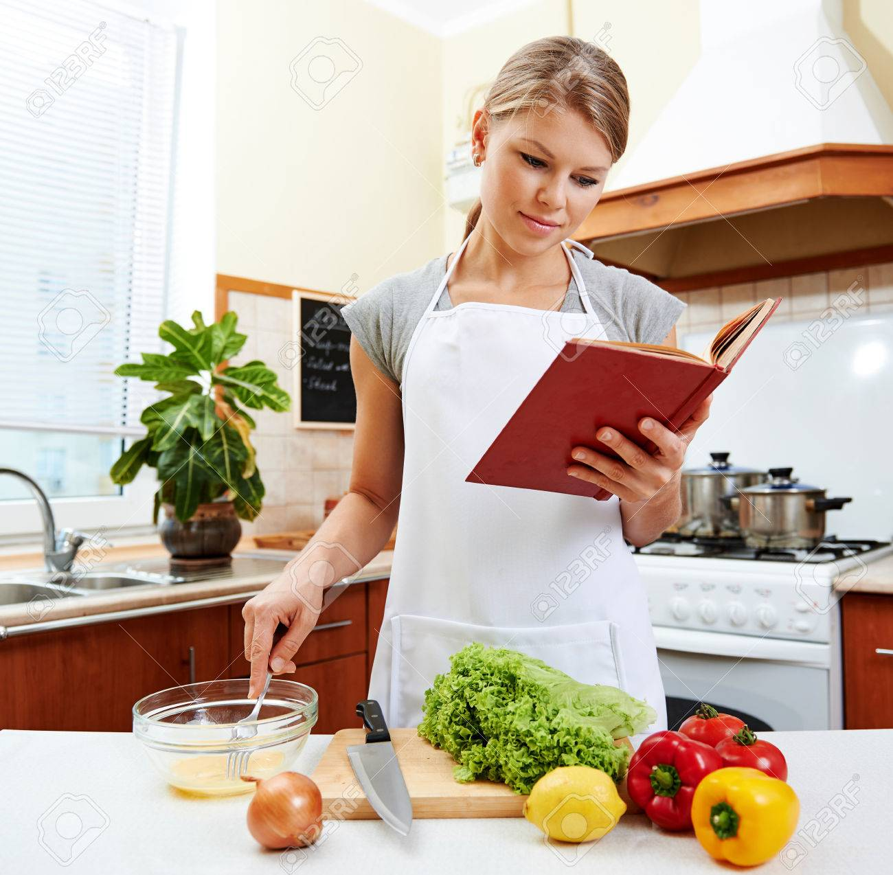 White apron food - Concentrated Female Reading Recipe Book And Cooking Meal Young Housewife Wearing White Apron Preparing Vegetable