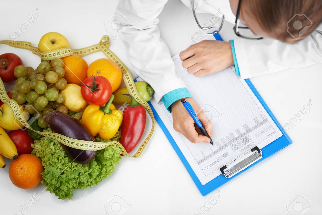 Doctor therapist writing case development form sitting at the desk in hospital. Female nutritionist prescribing diet to patient. - 48595938