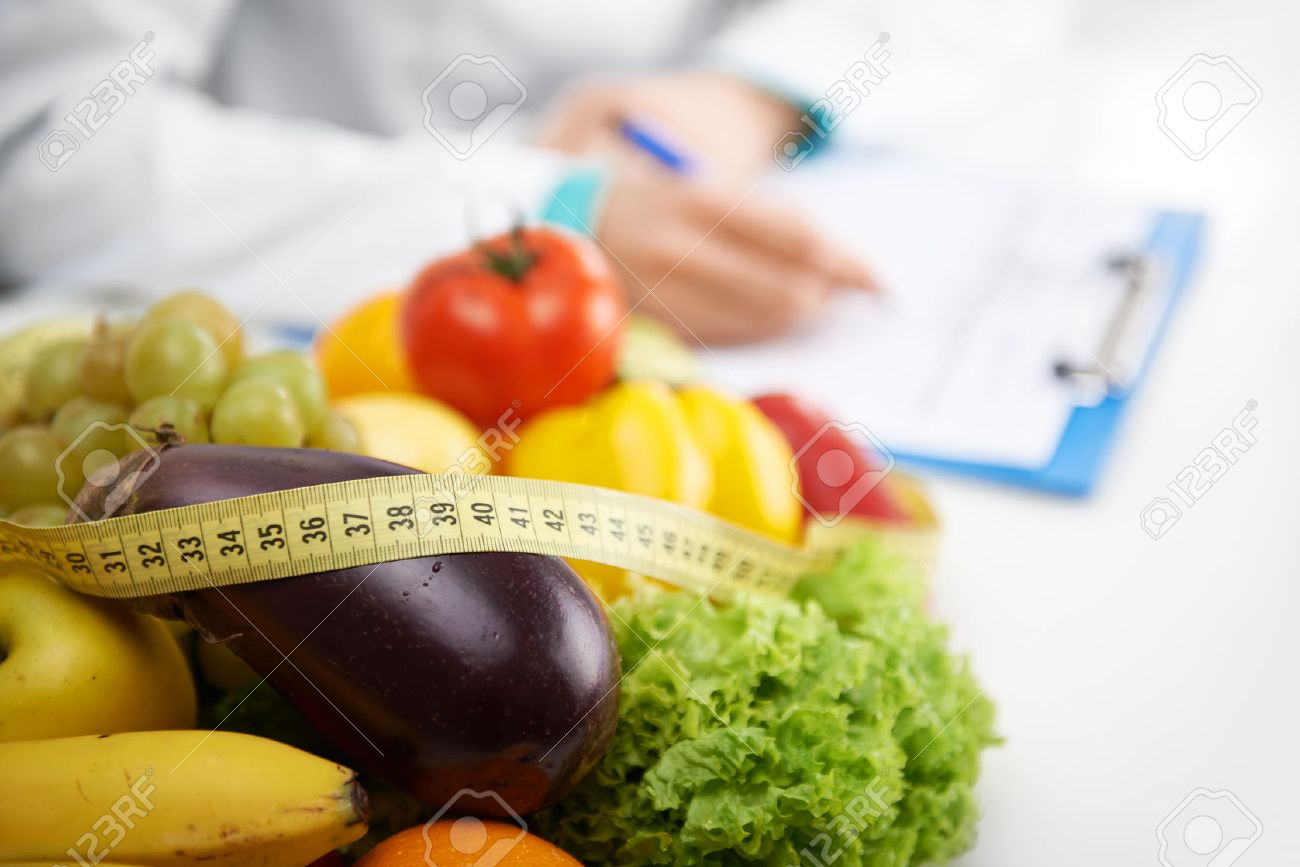 Healthy nutrition concept. Close-up of fresh vegetables and fruits with measuring tape lying on doctor's desk. - 48595947