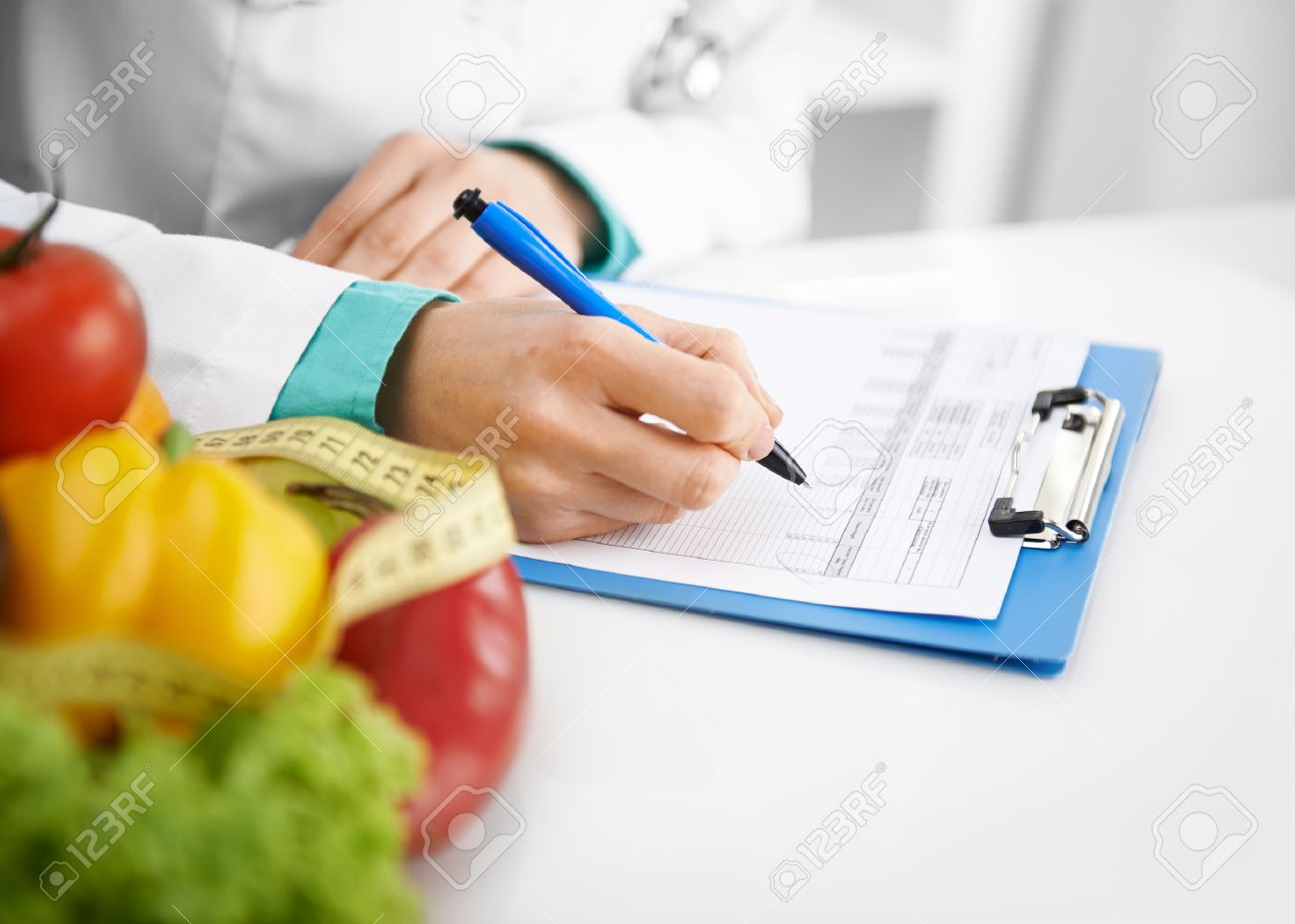 Doctor nutritionist writing case history in the office. Young woman dietitian prescribing recipe. - 48595948