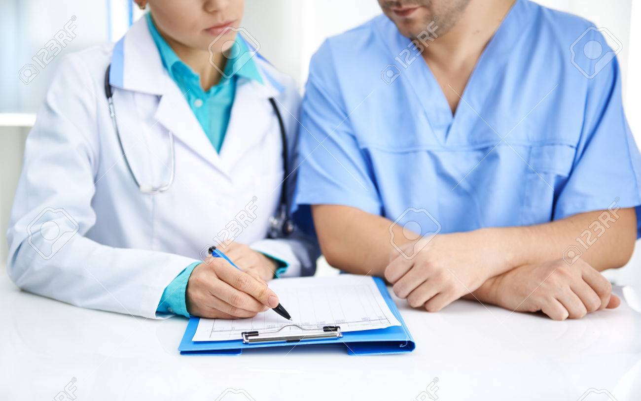 Portrait of two medical colleagues analyzing test result together in hospital. Young doctors team in uniforms working with documents at the desk. - 48597571