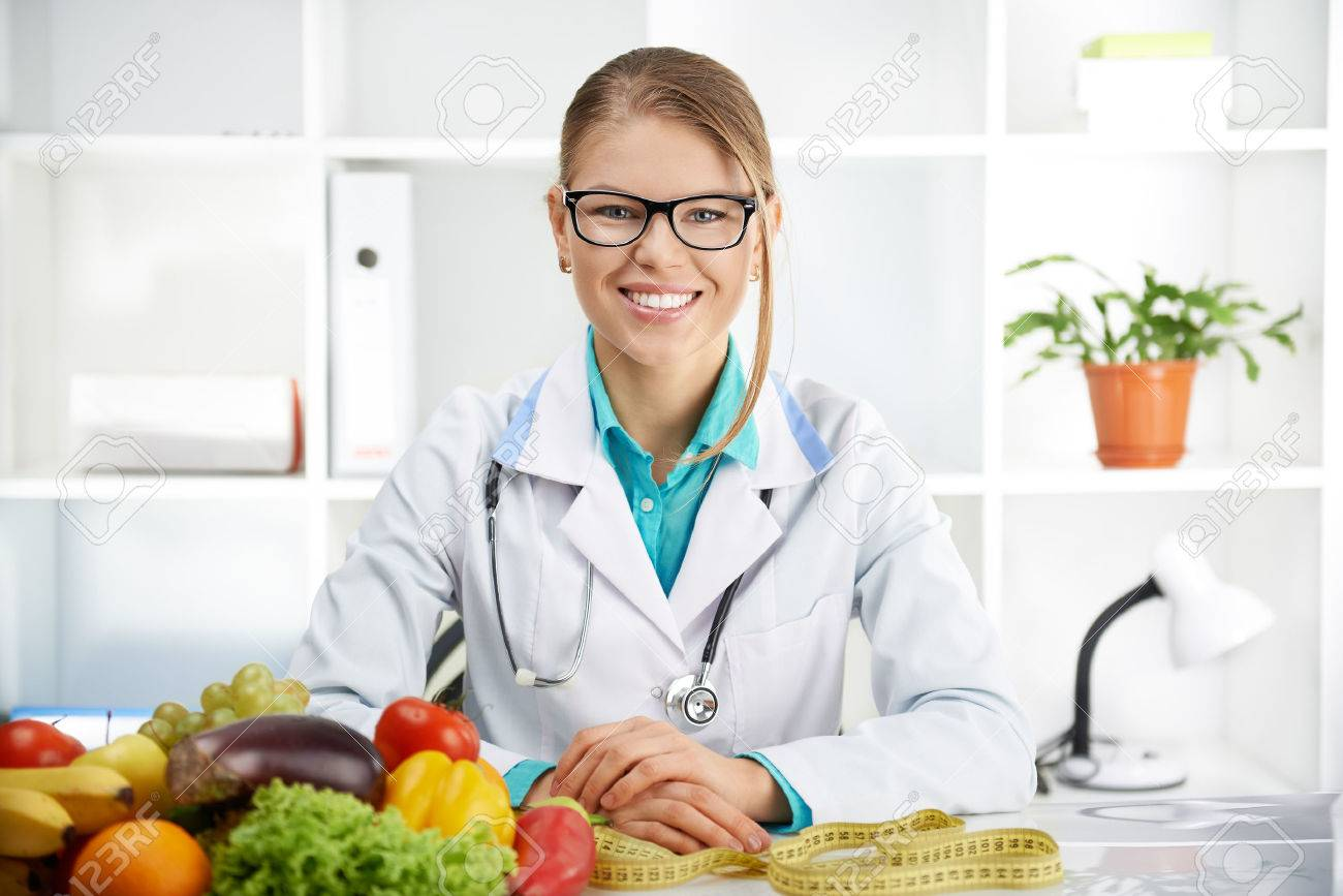 Smiling female dietitian sitting at the table with colorful fruits and vegetables in clinic. Concept of diet, lose weight and healthcare. - 48773806