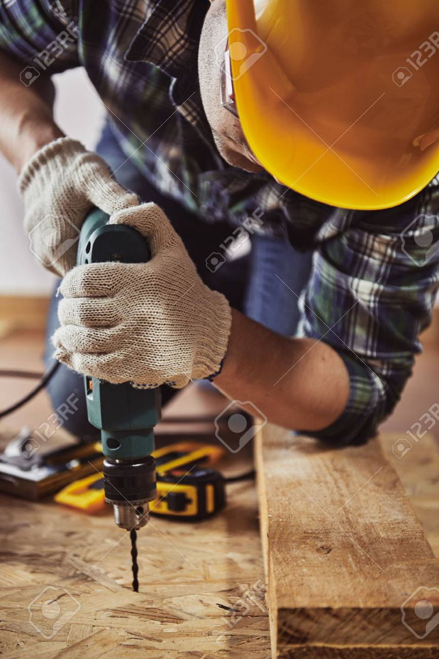 Young handyman in hardhat drilling wood in working studio. Concept of craft and technology. - 55392483