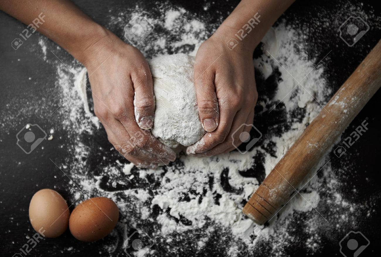 Chef hands kneading raw dough on the board in bakery. Woman cook preparing bread or pastry. - 55392491